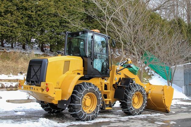 日本の雪の庭に黄色の雪ローダー大きな車