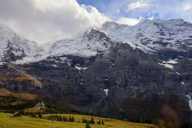 Вид на снежный альп горный пейзаж в осенней природе на швейцарском с поезда