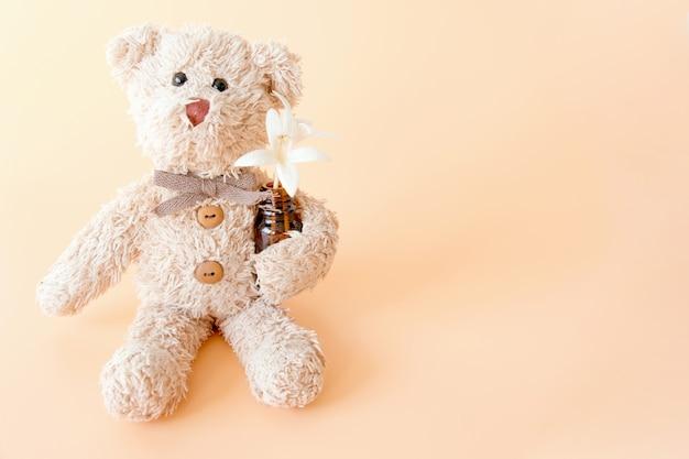 Симпатичный плюшевый медведь с цветами на пастельных фоне. счастливое животное, расслабляющее и наслаждающееся