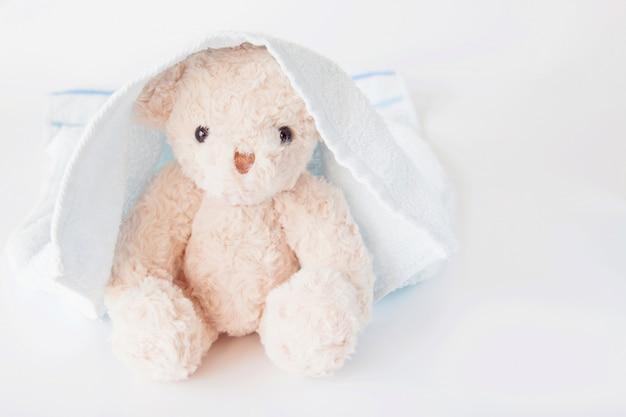 テディベアは、白い背景に青いタオルを覆った、かわいい人形は、風呂の後に爽やかな