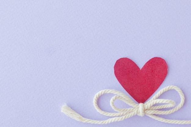 紫色の背景に弓ロープと赤い心