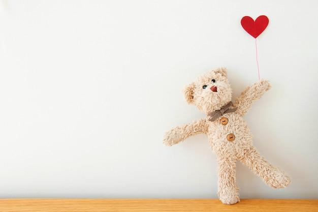 Милый плюшевый медвежонок с красным сердцем раздувает, счастливая концепция дня валентинки.