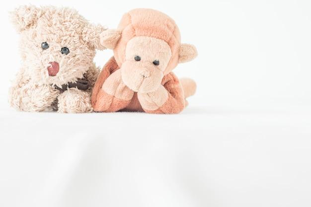 Пара куклы в отношениях, обезьяна и плюшевый мишка - лучшие друзья. влюбленная пара в любви на белом фоне
