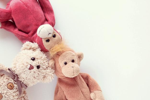Плюшевый медведь и пара обезьяны лежат