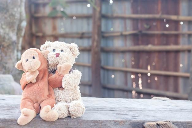 Мишка и милая обезьяна обнимаются на скамейке перед домом