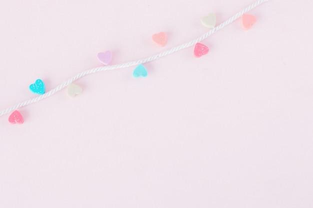 パステルの背景に白いロープでカラフルで甘いミニハート