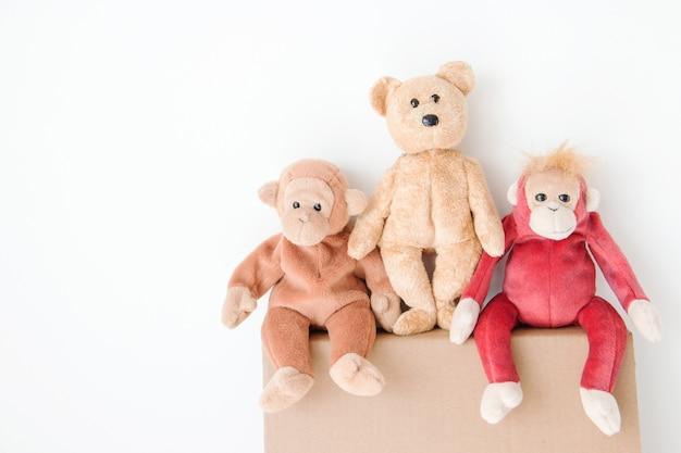 Симпатичный плюшевый мишка и пара обезьяны сидят на коричневой коробке
