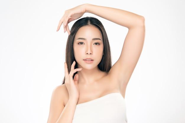 清潔で新鮮な肌と柔らかい頬と笑顔に触れる美しいアジアの若い女性。幸福と陽気で、白で隔離、美容と化粧品、