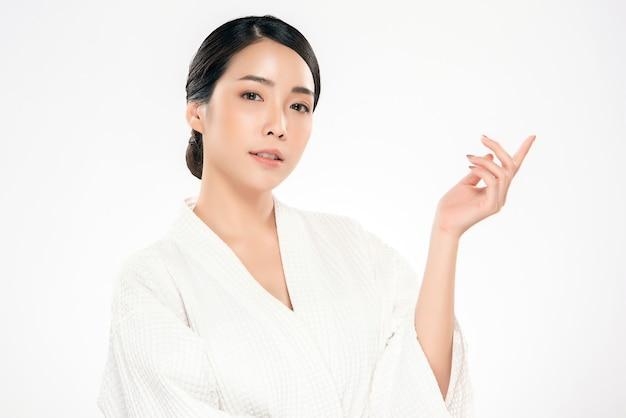 美しい若いアジアの若い女性は、ディスプレイ化粧品製品の陽気な手のひらを開きます。健康な肌、白、美容化粧品で隔離