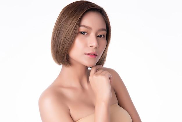 清潔で新鮮な肌と柔らかい頬と笑顔に触れる美しい若いアジア女性