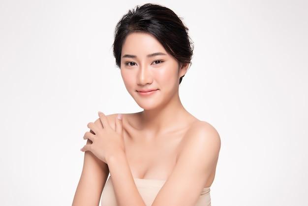 美しい若いアジア女性の手が肩に触れます。清潔で新鮮な肌