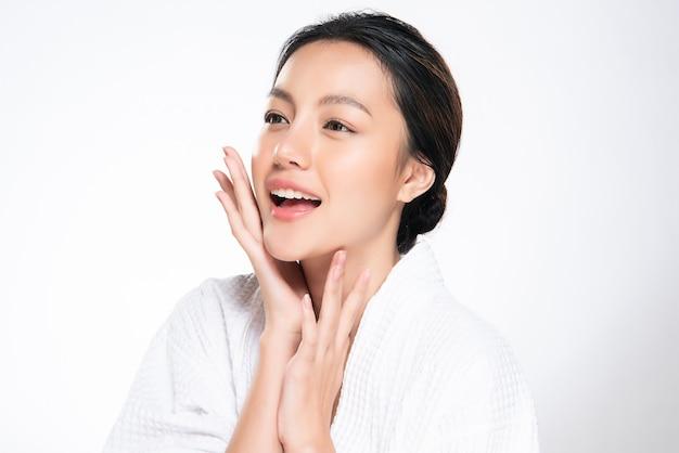 Красивая молодая азиатская женщина касаясь мягкой щеке и улыбке с чистой и свежей кожей. счастья и веселья, изолированных на белом, красота и косметика,