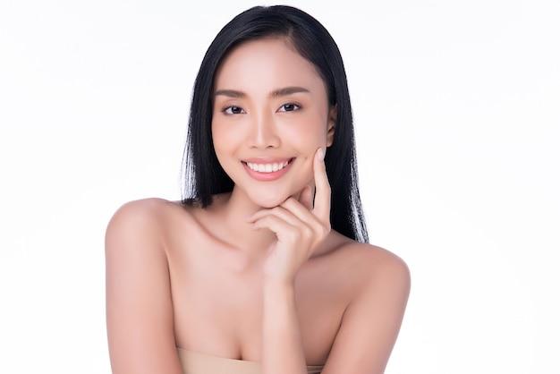 清潔で新鮮な肌と柔らかい頬と笑顔に触れる美しい若いアジア女性。幸福と陽気、、、美容と化粧品のコンセプト、