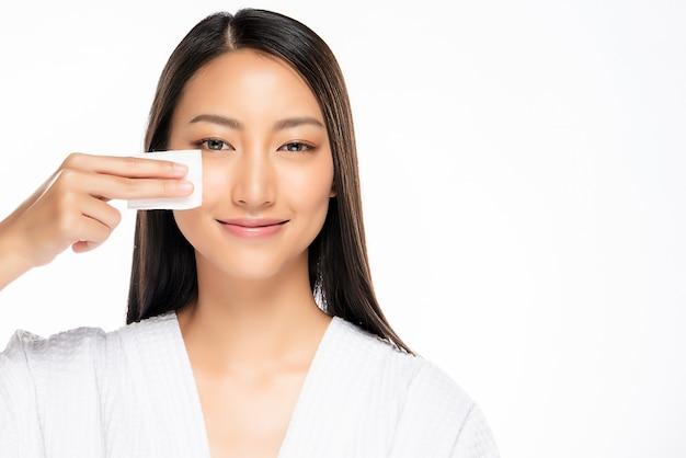 Счастливая усмехаясь красивая азиатская женщина используя изолированную кожу чистки ватного диска,
