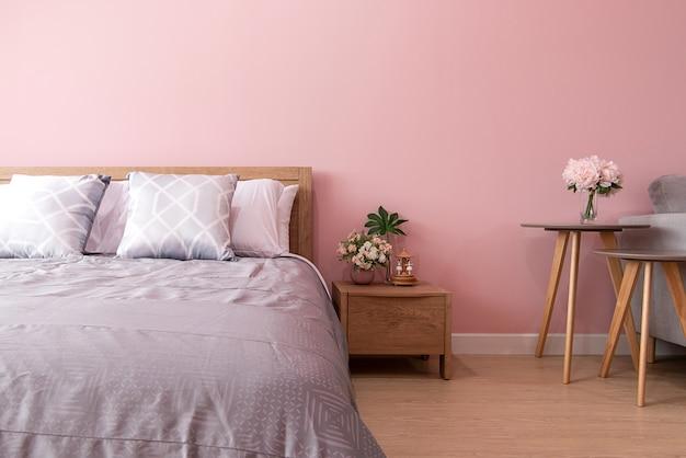 Интерьер спальни с удобной кроватью у розовой стены