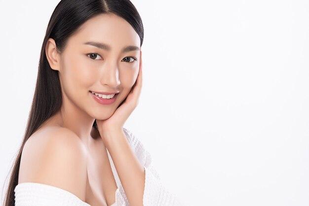 Красивая молодая азиатская женщина касаясь ее чистого лица с свежей здоровой изолированной кожей, косметикой красоты и концепцией ухода за лицом