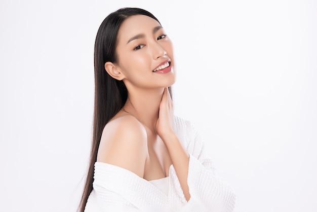 Красивая молодая азиатская женщина касаясь ее телу при свежая здоровая изолированная кожа, косметика красоты и концепция обработки лица.