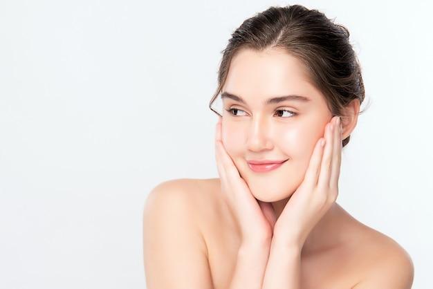 新鮮な健康な皮膚、分離、美容化粧品、フェイシャルトリートメントのコンセプトで彼女のきれいな顔に触れる美しい若い女性。