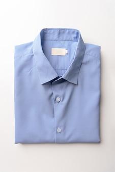 白に折り畳まれた新しいライトブルーのメンズシャツ
