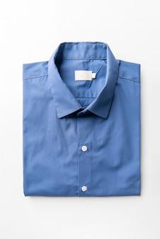 白に折り畳まれた新しいブルーメンズシャツ