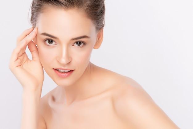 Красивая молодая женщина, касаясь ее чистое лицо со свежей здоровой кожей, изолированных на белом