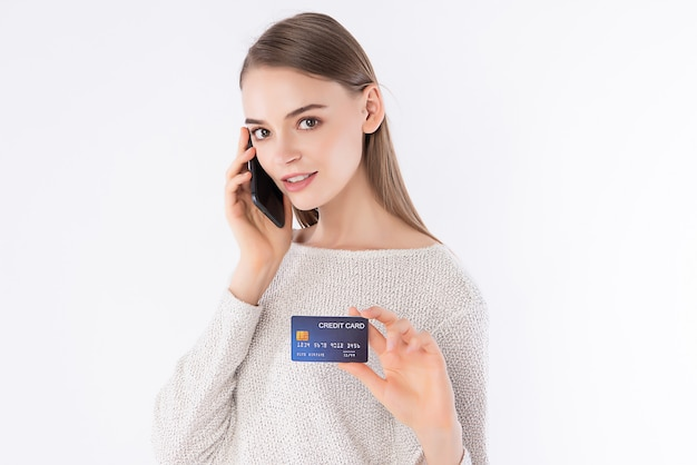 Работница с умным случайным взглядом представляя ее кредитную карточку.