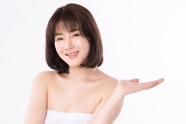 Красивые молодые азиатские женщины улыбаются и указывая к космосу экземпляра для дисплея счастье чувства продукта косметик при здоровая чистая и свежая изолированная кожа, концепция красоты.