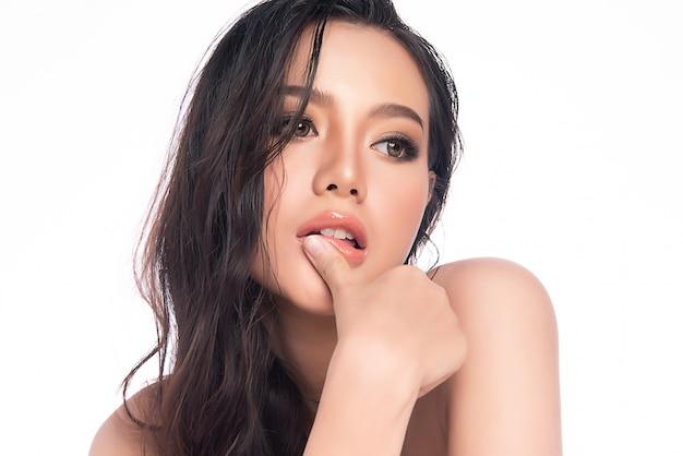 白い壁、美容化粧品、フェイシャルトリートメントのコンセプトに分離された新鮮な健康な肌で彼女のきれいな顔に触れる美しい若いアジア女性