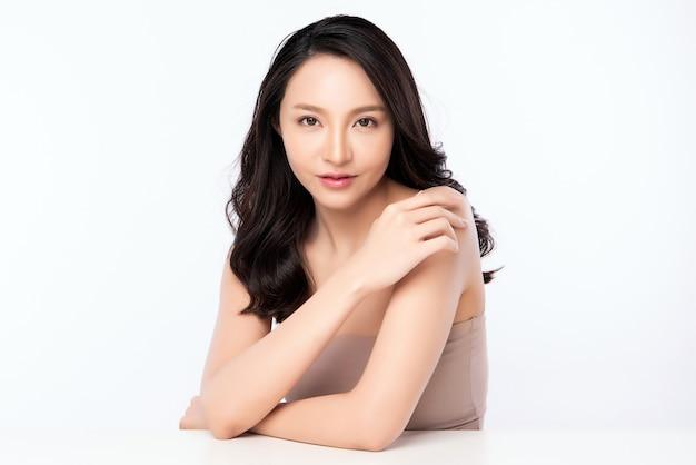 新鮮な健康的な肌、孤立した美容化粧品、フェイシャルトリートメントのコンセプトで彼女の体に触れる美しい若いアジア女性。