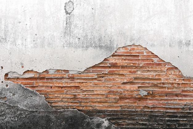 背景として灰色のセメント表面で覆われたひび割れたコンクリート壁。
