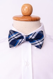 Галстук-бабочку ручной работы на фоне белой рубашки.