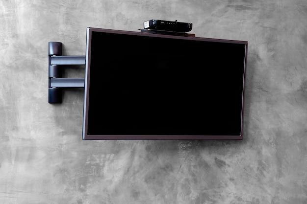 ケーブルテレビはセメントの壁にぶら下がってセット