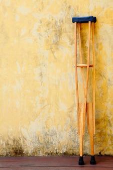 黄色いセメントの壁に頼る昔ながらの木製の松葉杖