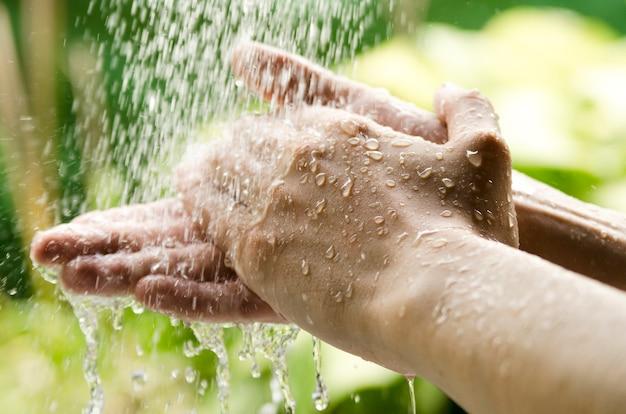 自然の水スプラッシュの下で男の手を洗う。