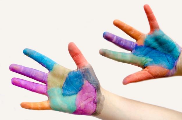 子供の手のひらの手は、さまざまな色で覆われて