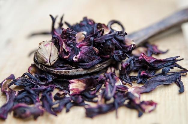 ハイビスカス乾燥花の茶が閉じます。スーダンは木製のスプーンで盛り上がった。胃の健康のためのハーブ。