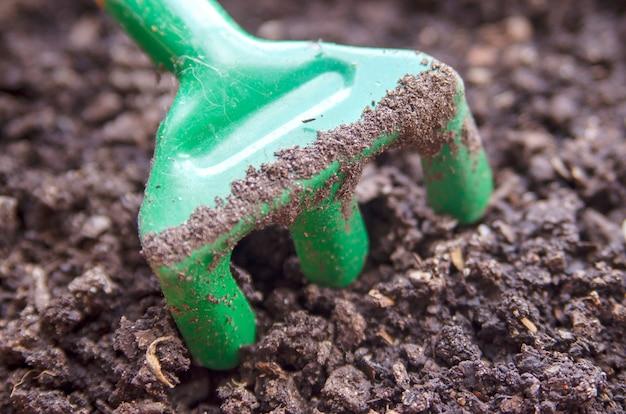 乾いた地面の土壌にある小さな緑色のプラスチックレーキ