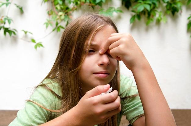 Маленькая девочка с синусом и головной болью. ребенок, имеющий проблемы со здоровьем на носу и синусит