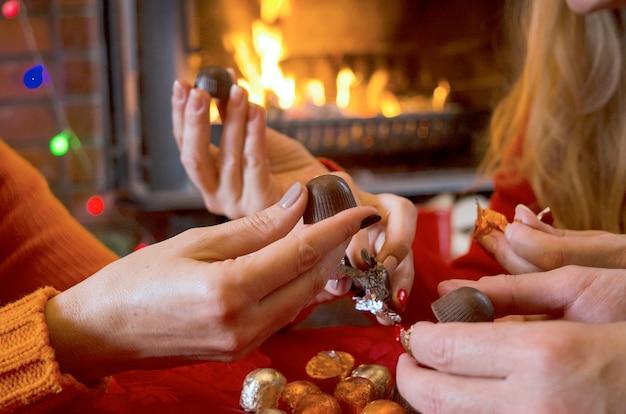 Друзья закрывают руки, открывают шоколадные лакомства у камина