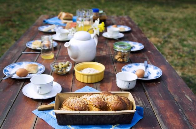 家の庭で木製のテーブルの上の甘いパンと朝食用食品。
