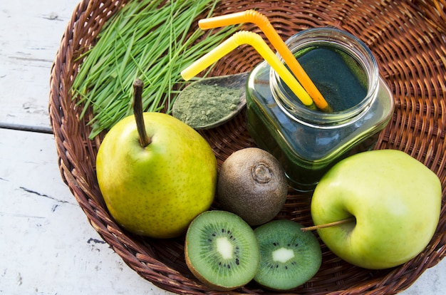 新鮮な緑の果実から小麦もやしと籐の皿の上のスプーンでパウダーを使った抗酸化ドリンク。