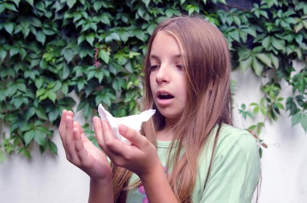 Девушка ребенка чихает в носовой платок в зеленом парке. у маленькой девочки аллергия на пыльцу или грипп.