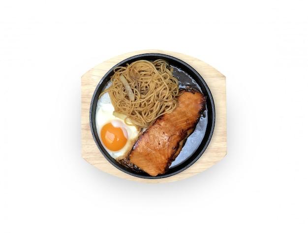 Стейк из лосося на гриле с жареным яйцом и спагетти лапша перец лук на горячей сковороде и деревянной тарелке диетическое блюдо