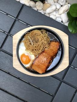 Стейк из лосося на гриле с жареным яйцом и спагетти лапша перец лук на горячей сковороде и деревянной тарелке