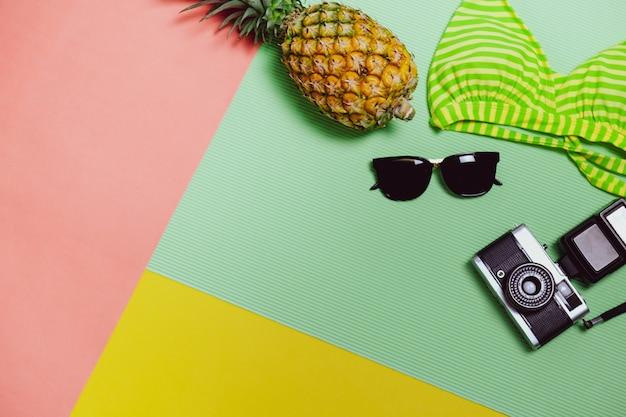 リラックスする時間はビーチに行き、パステルカラーの背景にサングラス、カメラ、ビキニ、パイナップルフルーツと一緒に旅行します。