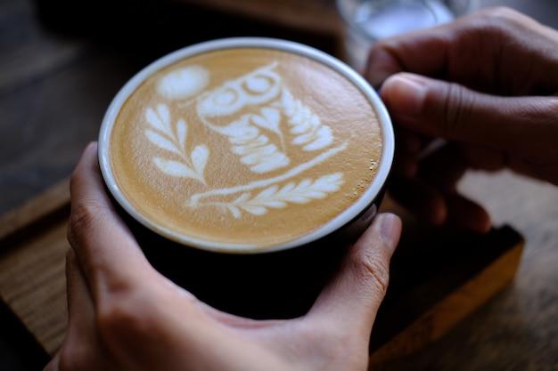 Рука держать чашку кофе. меню напитка для отдыха на деревянной текстуре стола