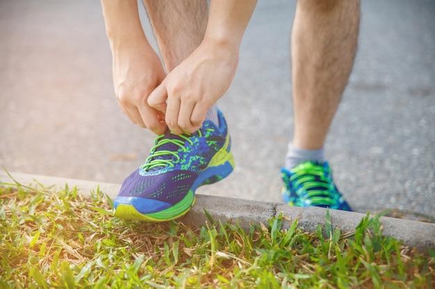 朝の運動のために実行する前にランニングシューズを結ぶ男ランナー。実行する準備をするために靴をチェックする男性ランナー。