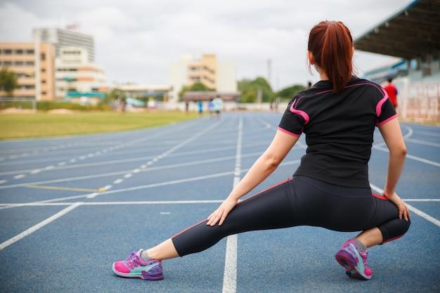 Женщины тренируются. молодая женщина фитнеса работая в солнечном ярком свете утром на голубой прорезиненной беговой дорожке.