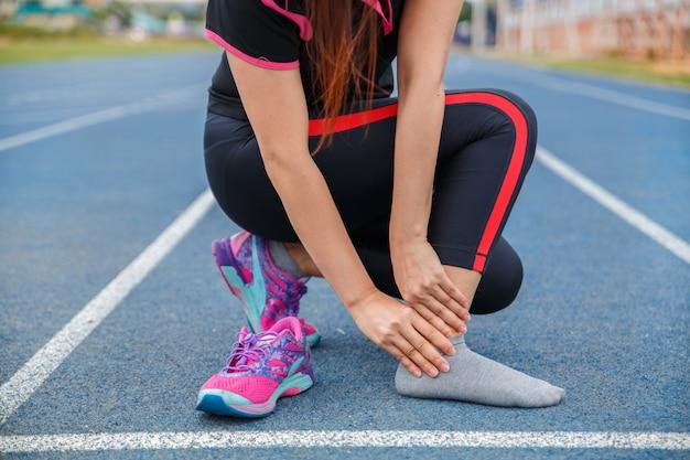 女性ランナーの足首の怪我と痛み。青いゴム引きランニングトラックで実行中に痛みを伴う足首に苦しんでいる女性。