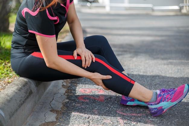 女性ランナーのアスリートの脚の怪我と痛み。道路を走っているときに痛みを伴う足に苦しんでいる女性。